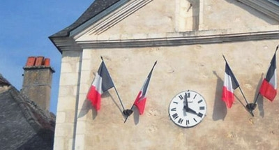 French flags and clock on building